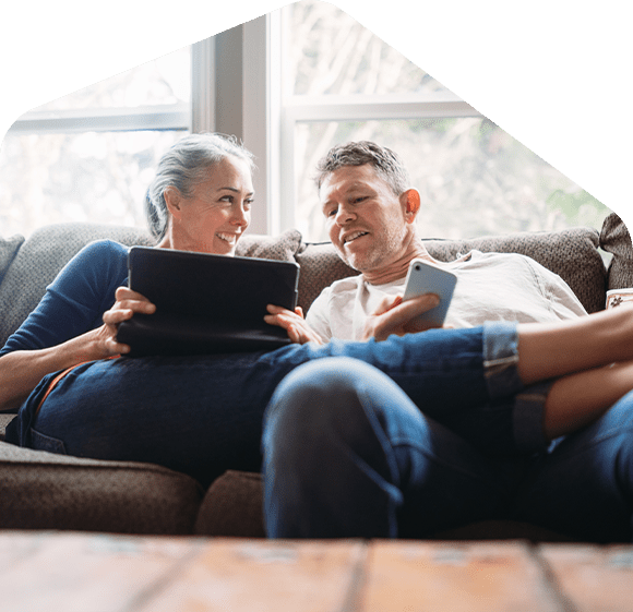 two-homeowners-using-gadgets-in-couch